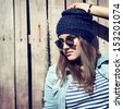 beautiful cool girl in hat and sunglasses against grunge wooden fence, toned and noise added - stock photo