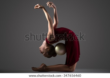 Beautiful cool young fit gymnast athlete woman in sportswear red dress working out, doing art gymnastics backbend exercise with white ball, full length, studio, dark background - stock photo