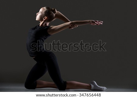 Beautiful cool young fit gymnast athlete woman in sportswear working out, doing art gymnastics, standing in backbend acrobatic exercise, Back Arch on her knees, full length, studio, dark background - stock photo