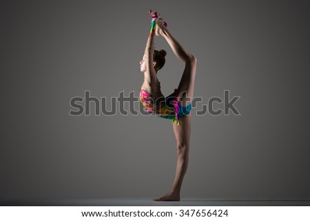 Beautiful cool young fit gymnast woman in colorful sportswear working out, standing on one leg, performing back scale, rhythmic gymnastics backbend element with maces, studio, dark background - stock photo