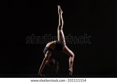Beautiful cool young fit woman in sportswear doing sport exercise, backbend, One-legged Upward Bow (Wheel) Posture, Eka Pada Urdhva Dhanurasana, full length, side view, studio shot, black background - stock photo