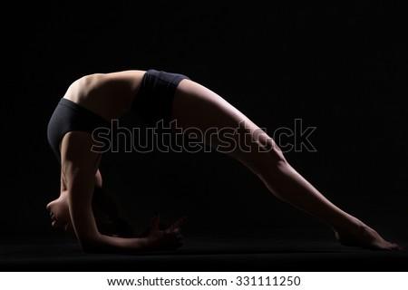 Beautiful cool young fit woman in sportswear doing sport exercise, Two-Legged Inverted Staff Pose, Upward Facing Two-Foot Staff Posture, Dwi Pada Viparita Dandasana, studio shot, black background - stock photo