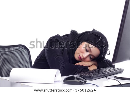 beautiful corporate muslimah woman with office attire showing tired expression while working on desktop computer - stock photo