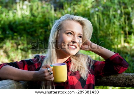 beautiful country blonde girl drinking from a yellow mug - stock photo
