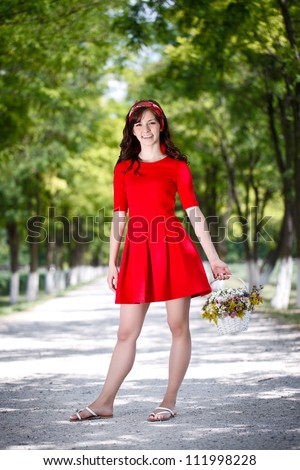 Beautiful country girl posing in red dress with flowers basket