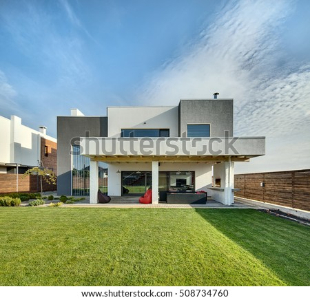 Beautiful country house in a modern style with the large lawn. In front of the house there is a covered terrace with a lounge zone and a furnace. On the lawn there is a tree and flowerbeds. Outside.