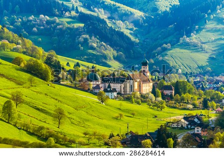 Beautiful countryside mountain landscape with a monastery in village. Germany, Black forest, Muenstertal. Toned - stock photo