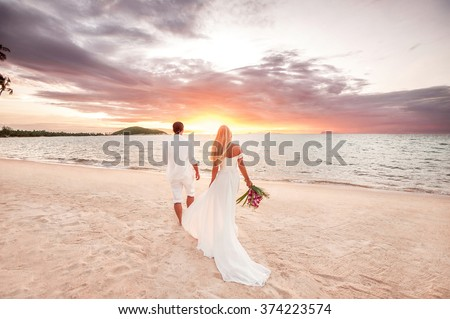 beautiful couple at sunset near the ocean.Honeymoon romantic couple in love holding hands walking on beautiful sunset at beach. Lovers or newlywed married young couple by the sea. Wedding in Thailand. - stock photo