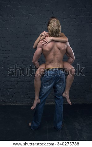 Beautiful couple. Beautiful young couple in love embracing indoor. Passionate couple, man and woman. Stand back. Back view of young embracing couple, man and woman. - stock photo