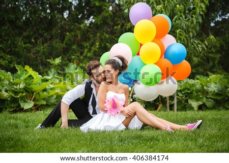 beautiful couple bride and groom sitting on the grass with colored balloons and laughing - stock photo