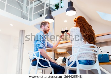 Beautiful couple celebrating moving in to new apartment by toasting wine - stock photo