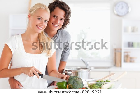 Beautiful couple cooking while looking at the camera - stock photo