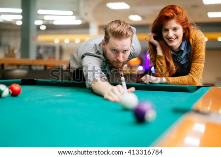 Beautiful couple dating and playing snooker - stock photo
