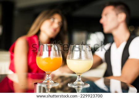 Beautiful Couple drinking aperitif in a Bar.