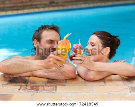Beautiful couple drinking cocktails in the swimming pool