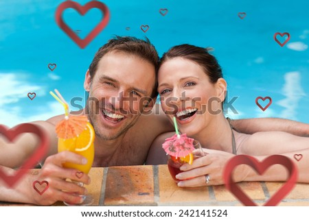 Beautiful couple drinking cocktails in the swimming pool against hearts - stock photo
