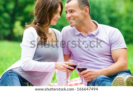 Beautiful couple drinks wine in park. Concept of romantic dating and love - stock photo