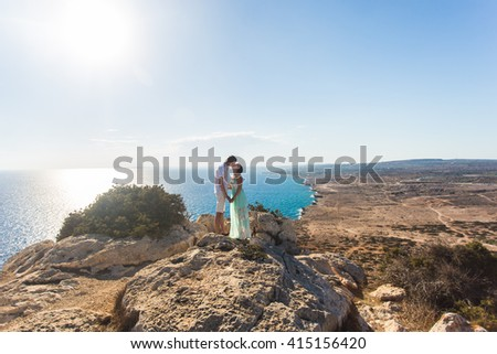 beautiful couple embrace on a stones and  background of the sea
