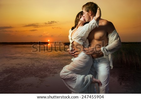 Beautiful couple embracing and kissing against sea sunset  - stock photo