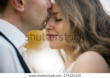 beautiful couple enjoying embrace of each other and tenderly smiling - stock photo