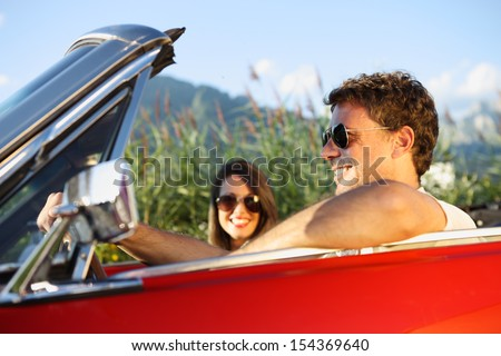 Beautiful couple enjoying in a convertible car ride - stock photo