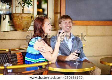 Beautiful couple enjoying their red wine in a cafe - stock photo