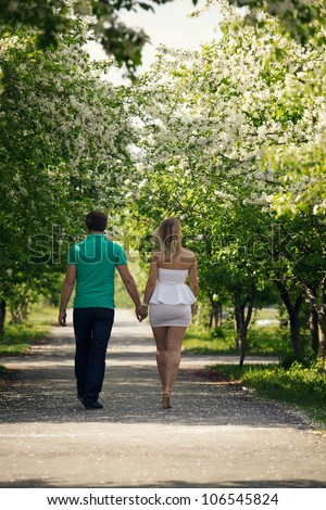 Beautiful couple having a stroll in park at spring