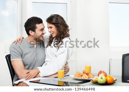beautiful couple having breakfast table, girl sits on hands for a boyfriend - stock photo