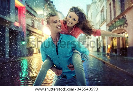 Beautiful couple having fun on a rainy day - stock photo