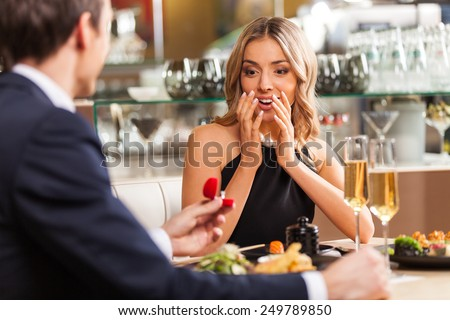 Beautiful couple having romantic dinner at restaurant. back view of man proposing to woman in restaurant - stock photo
