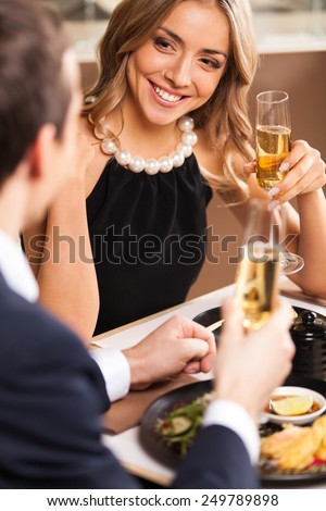 Beautiful couple having romantic dinner at restaurant. smiling woman looking at man dinking wine at toast - stock photo