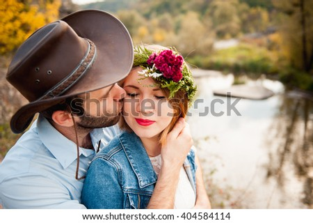 beautiful couple hugging each other near a mountain river. guy in a cowboy hat and a girl in a dress and denim jacket - stock photo
