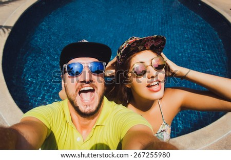beautiful couple in caps and sunglasses make the selfi to the camera compared to the pool - stock photo