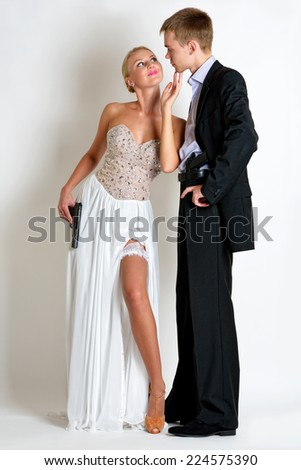 beautiful couple in evening dresses  with a guns. Photoshooting in criminal and a spy style. - stock photo