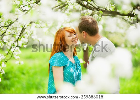 beautiful couple in love having fun outdoors in spring garden full of blooming apple-trees - stock photo