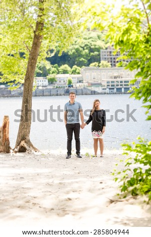 Beautiful couple in love holding hands under big tree at riverbank - stock photo