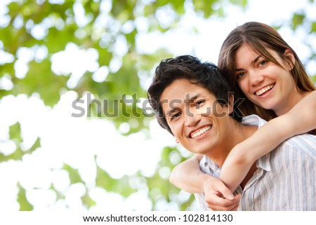Beautiful couple in love hugging outdoors and smiling - stock photo