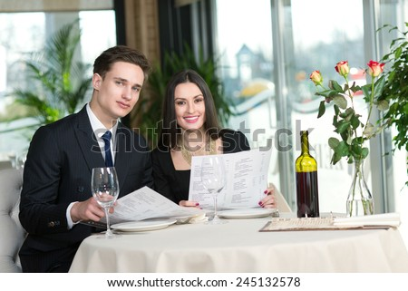 Beautiful couple in love is having romantic dinner together. Both are reading menus and smiling - stock photo