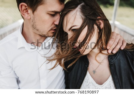 Beautiful couple in love near a cozy log cabin. Hugging, holding hands of each other. close-up face portrait