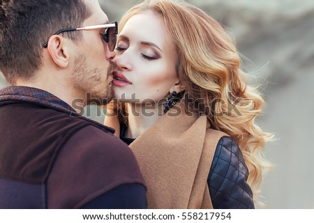 Beautiful couple in love on Valentine's Day. Happy young couple walking on the sandy mountains on a cloudy day