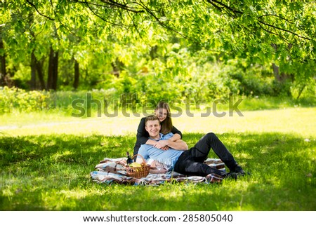 Beautiful couple in love relaxing under big tree at park