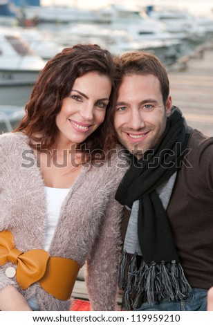 Beautiful couple in love sitting on wooden pier in marina - stock photo