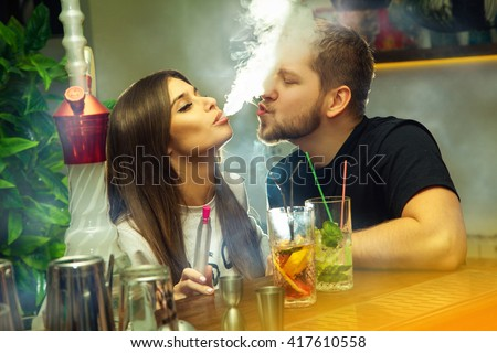 Beautiful couple in love smokes hookah and drinks cocktails in the bar - stock photo