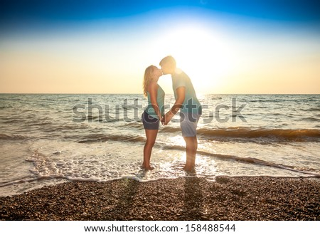 Beautiful couple in love standing in water and kissing against sun - stock photo