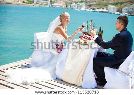 Beautiful couple in love the bride and groom posing on the bridge at the sea at the wedding table decorated with exotic bottles and wooden model ship. Enjoy a moment of happiness and love. - stock photo