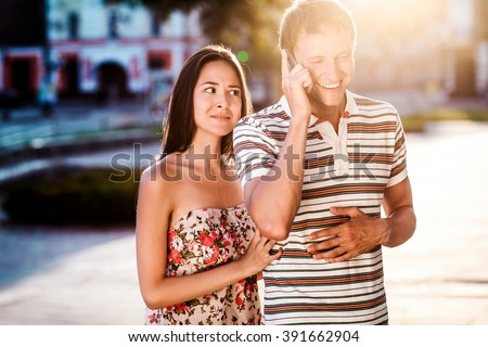 beautiful couple in love walks down the street, a Man talks on his mobile phone. The concept of good mood - stock photo