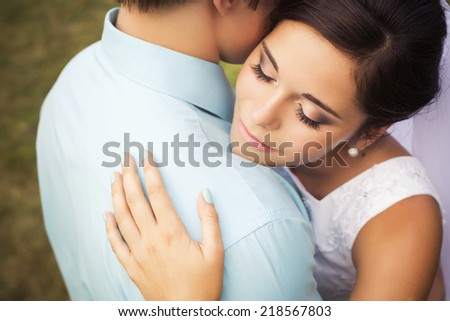 Beautiful couple in love. Wedding day. Wedding dress. Tiffany blue and white colors. Bouquet of roses. Park outdoors. Copy space