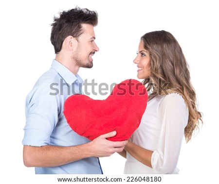 Beautiful couple in love with heart pillow, isolated on white background