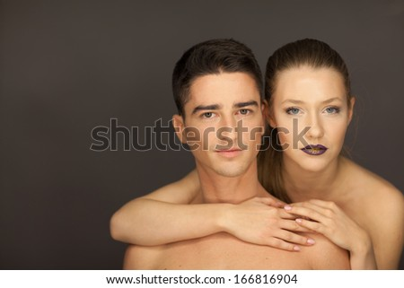 beautiful couple in studio portrait front view pose for the camera, the woman behind