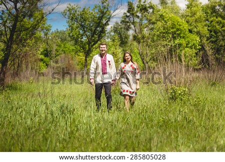 Beautiful couple in traditional slavic clothes walking at meadow